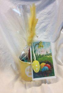 Bilde av en påskehilsn med kort, fjær, egg og kopp med godteri.
